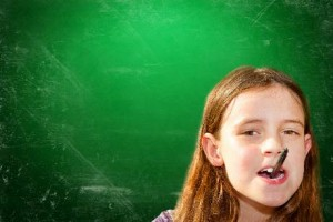 schlaues Mädchen mit Hochbegabung steht vor einer Schultafel mit Stift im Mund