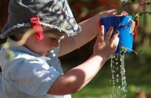 Kleinkind spielt mit Wasser in der Sonne Frühpädagogik Kleinkindpädagogik