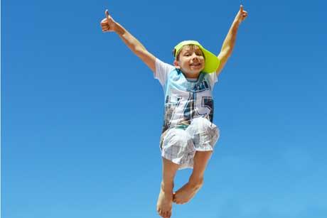 Glückliches Kind voller Selbstbewusstsein jubelt beim Hüpfen