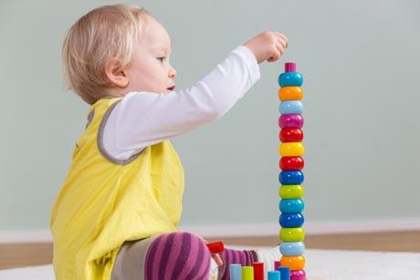 Kleinkind spielt mit Bauklötzen konzentriert allein Pikler