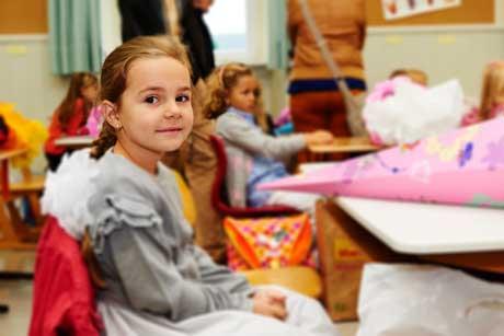 Erster Schultag Mädchen im Klassenzimmer mit Schultüte und Schulranzen