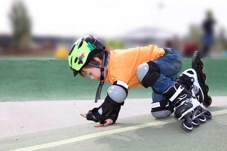 Kind nach Sturz beim Skaten aufstehen hinfallen