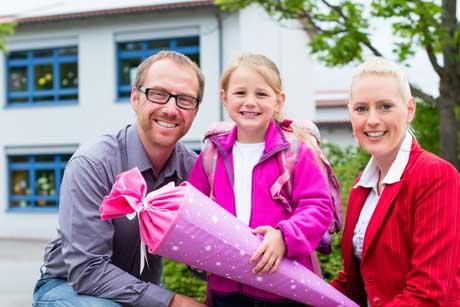 Rituale zur Einschulung - erster Schultag Eltern bringen Tochter mit Schultüte in die Schule