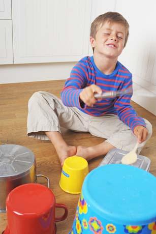 Junge spielt Schlagzeug auf Töpfen und Schüsseln aus purer Freude
