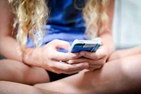 junges Mädchen am Smartphone - immer mehr Jugendliche leiden unter Internetsucht