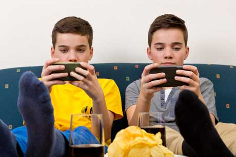 Kinder und Jugendliche zocken gerne piele-Apps - Zwei Jungen mit Smartphone auf der Couch
