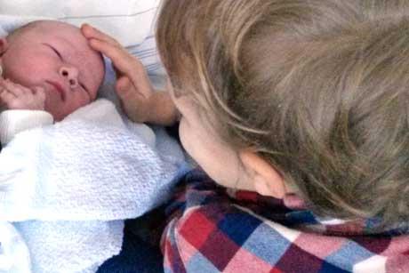 Kind mit neu geborenem Geschwisterchen Baby
