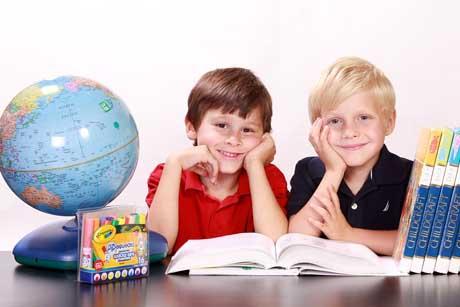 Gesundes Lernen macht Spaß - zwei Jungen mit Globus und Büchern schauen glücklich