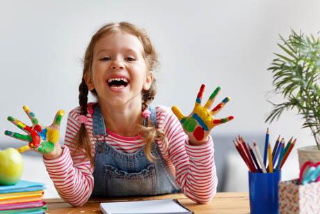 Kreativität bei Kindern fördern - Mädchen mit bunter Farbe an den Händen lacht