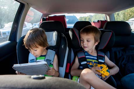 Helikopter-Eltern Two boy in children car seats, traveling by car and playing with toys and tablet, summertime