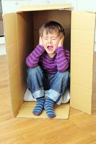 Kind in Karton, überfordert, hält sich die Ohren zu
