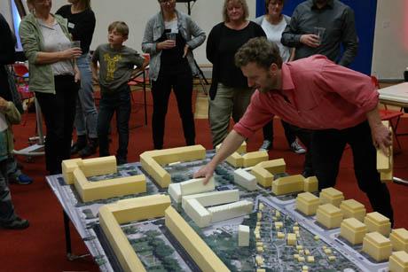 Lehrer, Schüler und Architekten diskutieren Baupläne anhand eines Architekturmodells.
