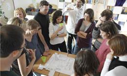 Lehrer und Architekten stehen um einen Tisch mit Bauplänen