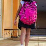Ein Mädchen mit Schulranzen auf dem Weg zur Schule