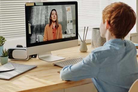 Nachhilfe per Videokonferenz Online Junge sitzt vor Computer mit Online-Nachhilfe