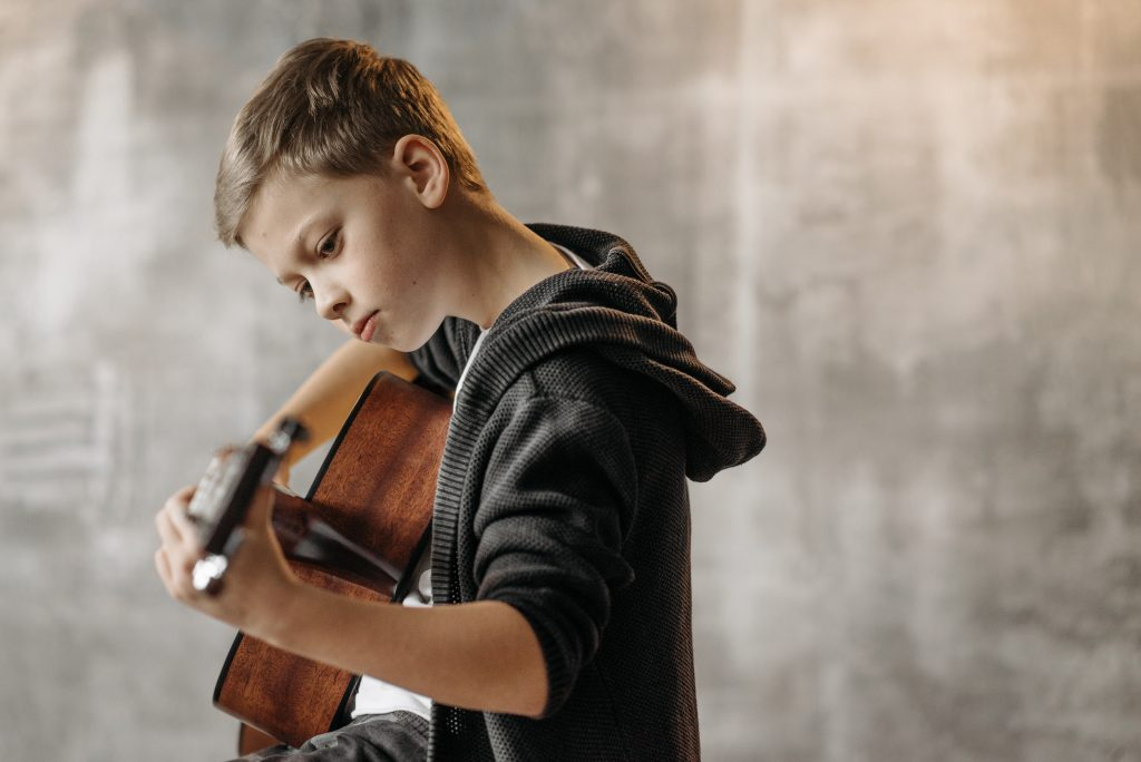 Die Gitarre ist das Lieblingsinstrument der Deutschen. Ein Junge spielt konzentriert Gitarre.