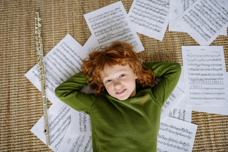 Musikunterricht für Kinder Junge liegt auf Noten mit Querflöte